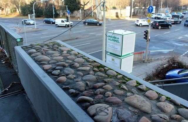 Grauer Pflanztrog ohne Pflanzen. Er hat eine Oberfläche aus fest einbetonierten Steinen. Im Hintergrud eine Filteranlage für Feinstaub und Fahrzeuge auf der Kreuzung am Neckartor.
