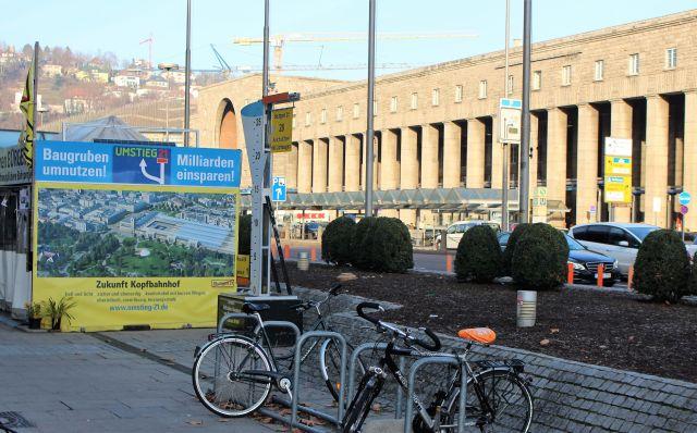 Gegenüber dem Stuttgarter Hauptbahnhof, der im Sonnenlicht liegt, steht eine Hütte der S21-Gegner mit der Aufschrift 'Baugruben umnutzen'.