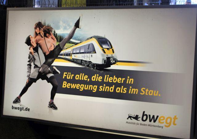 """Werbung mit dem Text """"Für alle, die lieber in Bewegung sind als im Stau"""". Eine moderne Bahn mit zwei tanzenden Menschen."""