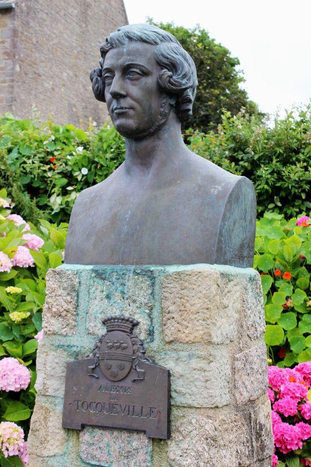 Denkmal für Alexis de Tocqueville im gleichnamigen französischen Ort. Die dunkle Skulptur zeigt ein freundliches Gesicht - umgeben von einer lockigen Haarpracht.
