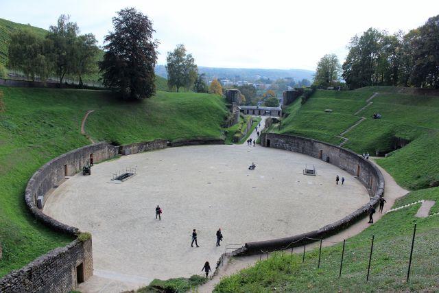 Die mit Sand belegte Arena ist der zentrale Bereich des Amphitheaters. Es ist von einer 4 Meter hohen Mauer umgeben. Über dieser erheben sich die Zuschauerränge.