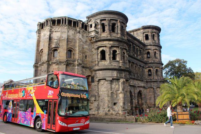 Die Porta Nigra, erbaut aus weißem Sandstein. Links daneben ein Bus für Touristen, der auch auf die Marx-Ausstellungen hinweist.