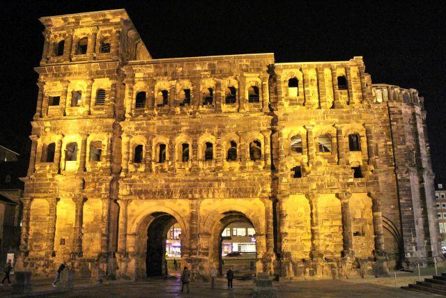 Goldfarben schillert die Porta Nigra bei dieser Nachtaufnahme.