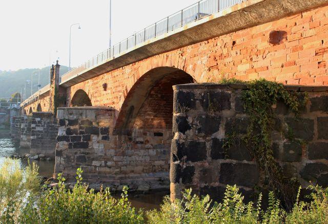 Brückenpfeiler aus Basaltquadern und darüber gemauerte Steine. Darüber die moderne Straßenbrücke.