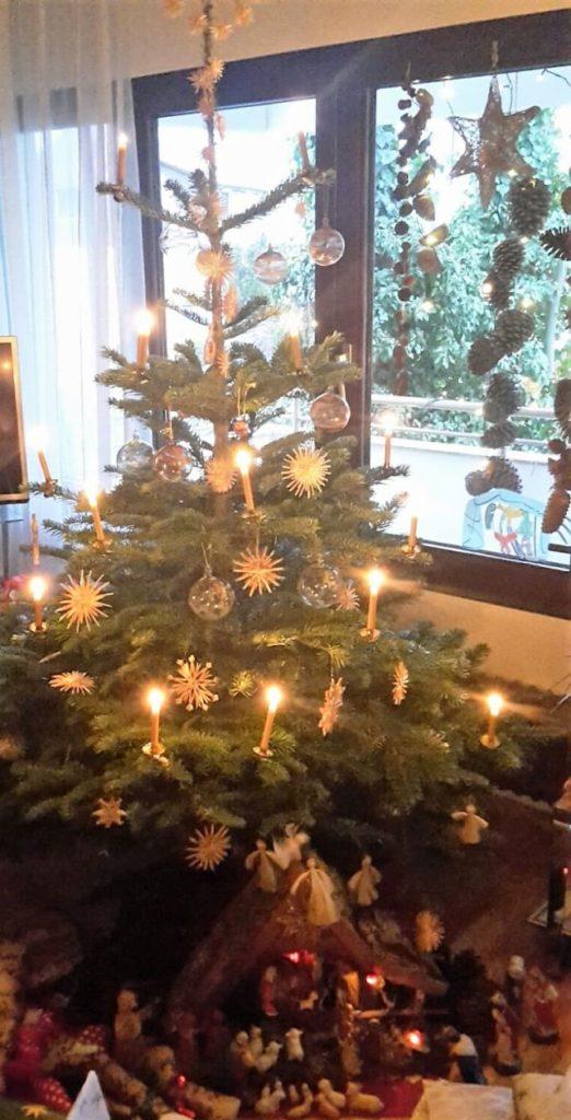 Weihnachtsbaum mit brennenden Kerzen und Glaskugeln.