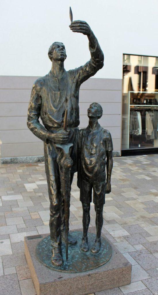 Eine dunkle Skulptur mit zwei Figuren. Der Meister zeigt dem Lehrling ein Werkzeug.
