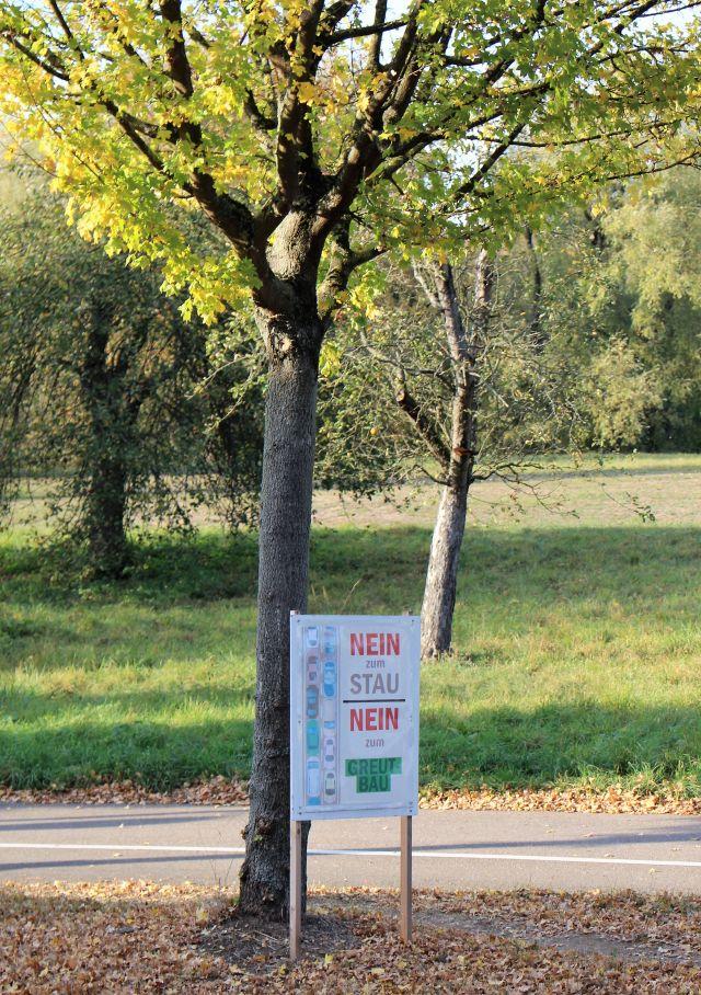 Vor einem Baum mit grünen Blättern steht ein Plakat: 'Nein zum Stau - nein zum Greut-Bau'.