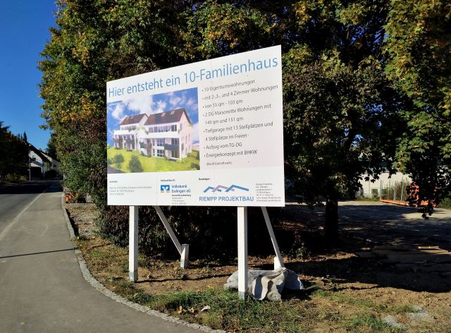 Informationstafel am Baugrundstück mit der Werbunf für das Zehn-Famuilien-Haus, das heir errichtet wird. Davor noch Büsche und Bäume, die inzwischen verschwunden sind.