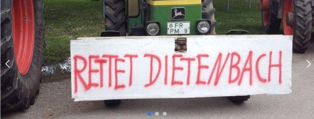 Transparent 'Rettet Dietenbach' vor einem älteren Traktor.