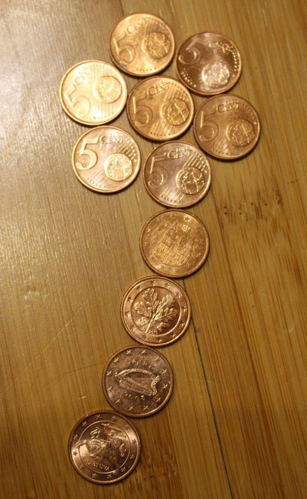 Fünf-Cent-Münzen angeordnet auf hellem Holz wie eine Blume mit Stil.
