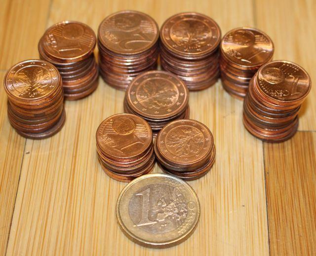 Kleine Säulen mit Ein- und Zwei-Cent-Münzen umgeben ein Ein-EURO-Stück.