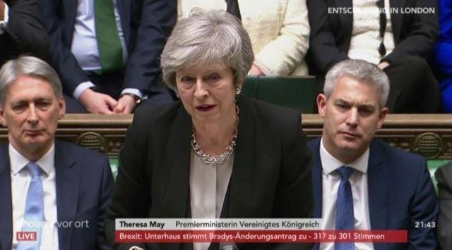 Theresa May mit grauen Haaren in der Debatte, links und rechts Minister ihrer Regierung.