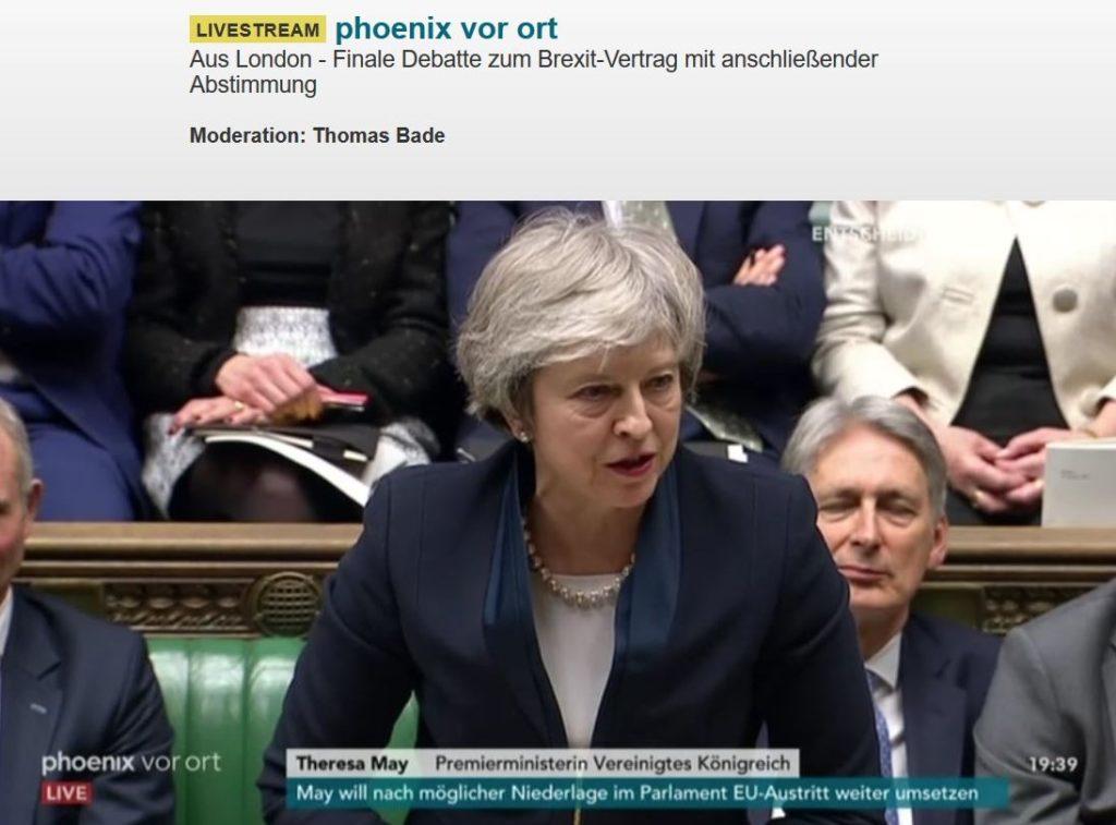 Theresa May mit grauen Haaren und dunklem Blazer. Im Hintergrund weitere Abgeordnete.