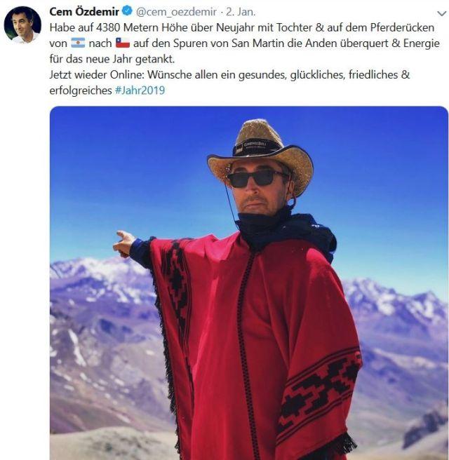 Cem Özdemir mit Sonnenbrille, breitkrempigem Hund und ritem Poncho vor der Bergkulisse.