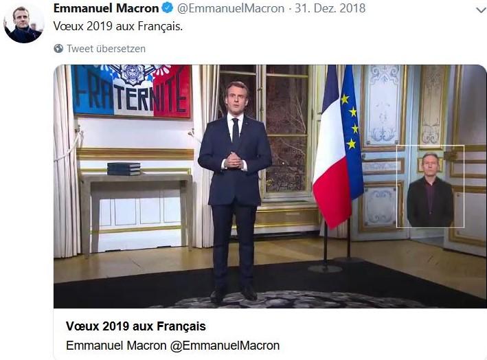 Macron im Anzug mit Krawatte, stehend. Neben ihm die französische Flagge und ein Bild mit der Inschrift Fraternité.