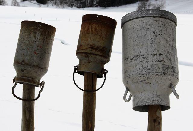 Drei unterschiedlich große Milchkannen stehen auf dem Kopf auf einzelnen Holzpfählen. Im Hintergrund eine mit Schnee bedeckt Landschaft.e