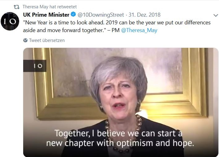 "Theresa May mit grauen Haaren vor einem nicht erkennbaren Bild, man sieht nur den goldenen Rahmen. Text: ""Together, I believe we can start a new chapter with optimism and hope""."