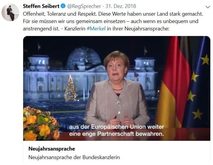 Angeöa Merkel sitzend, neben ihr die deutsche Flagge und auf der anderen Seite gelbliche Blumen.