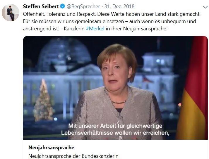 Angela Merkel mit deutscher Flagge und Blumen bei der Neujahrsansprache.