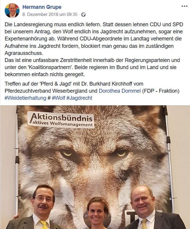 Grupe u.a. vor einem Plakat 'Aktionsbündnis aktives Wolfsmanagement'.