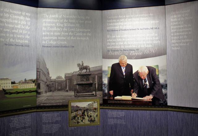 Ian Paisley bei der Unterschrift im Gedenkbuch. Daneben Bertie Ahern. Im HintergrundInformationstafeln.