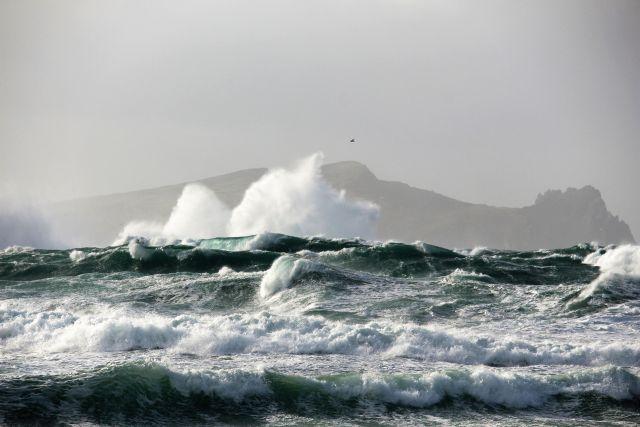 Im Hintergrund eine Insel, die schmenenhaft wie ein schlafender Riese aussieht. Im Vordergrud auflaufende Wellen und hohe Wellenberge.