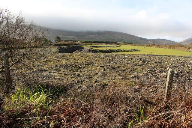 Ein Graben durchzieht eine Weidefläche. Hier werden Rohre verlegt, um die Wiese wieder als Weidefläche nutzen zu können. Am Rande noch einige Büsche und alter Pflanzenbestand.