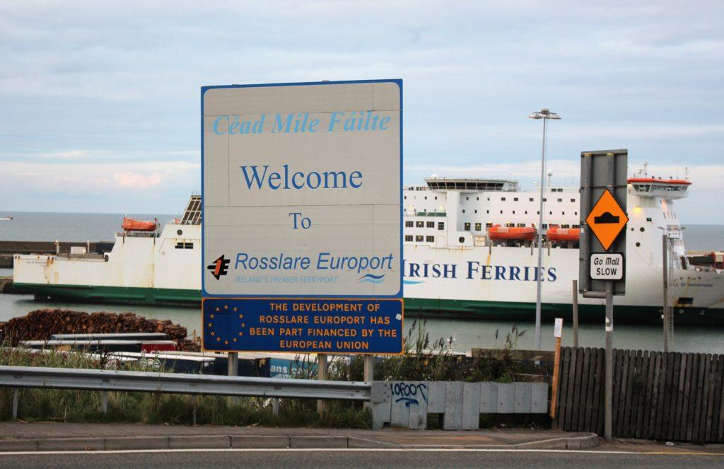 Im Vordergrund ein Schild mit dem Hinweis auf die EU-Förderung des Hafens in Rosslare, dahnter eine Fähre von Irish Ferries.