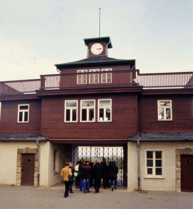 Zugang zum ehemaligen KZ Buchenwald. Eine Besuchergruppe geht gerade durch das schmiedeeiserne Tor. Der Durcghang befindet sich in einem Gebäude mir rotbrauner Holzfassade.