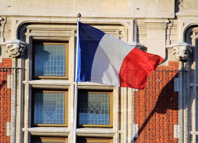 Blau-weiß-rote Flagge FRankreichs am Rathaus von Calais. Direkt vor einem Fenster und der Hauswand im Wind flatternd.