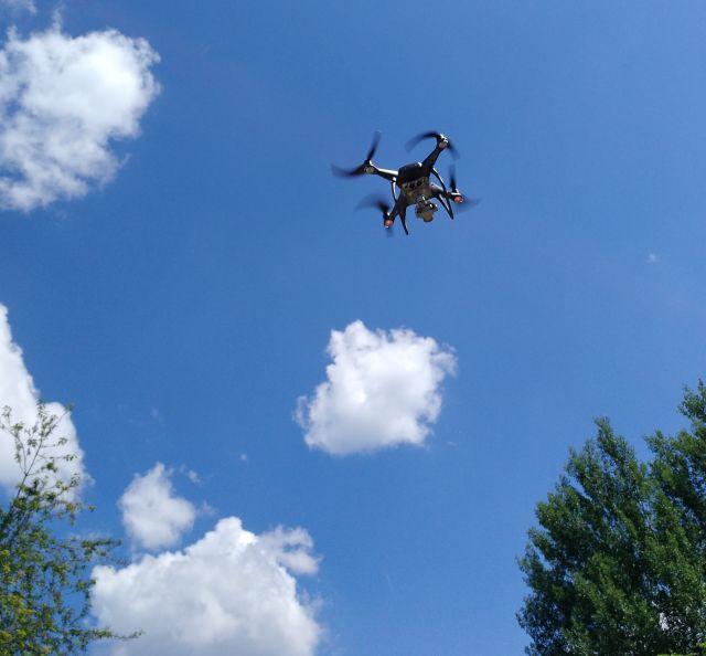 Kleine Drohne mit Kameraausstattung in niedriger Höge vor einem blauen Himmel mit wenigen weißen Wolken.