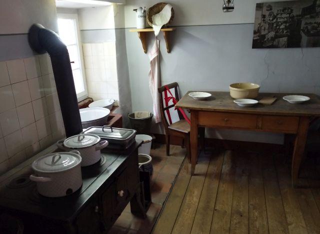 Küche der Familie Ebert. Der Spülstein ist noch im Original erhalten. Auf dem Esstisch stehen einige Teller, auf dem Kohlenherd zwei Töpfe.