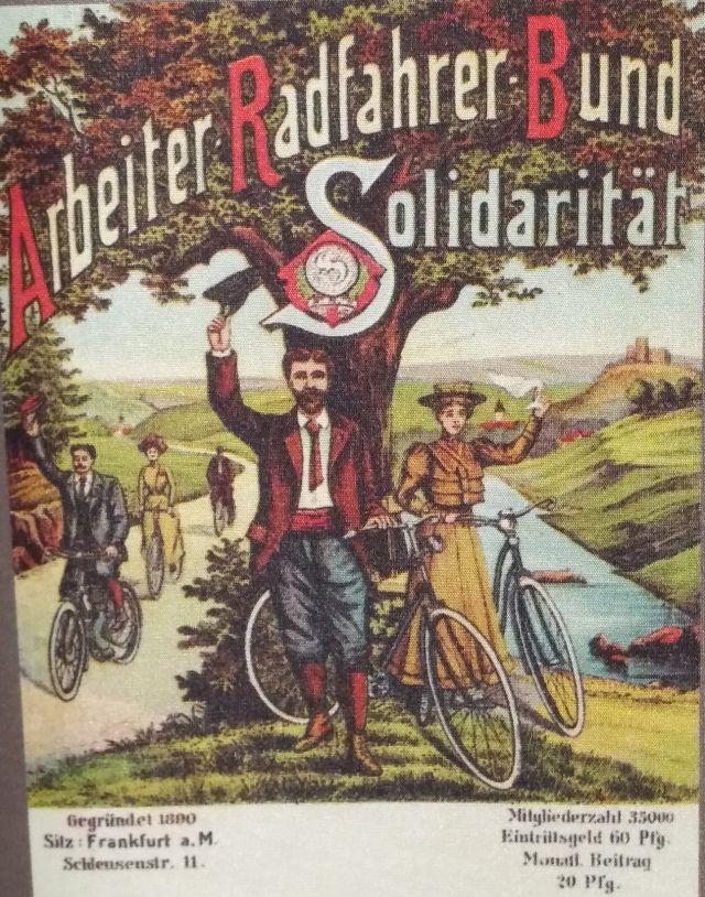 Auf dem Plakat sind gemalte FahrradfahrerInnen mit Hut und Krawatte zu sehen.