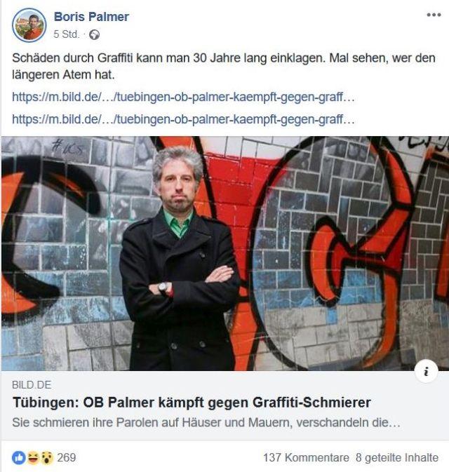 Oberbürgermeister Palmer vor einem Graffito. Er trägt ein Jacket und hat graue Haare und Bart.