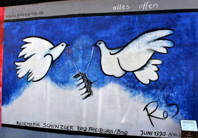 Zwei Friedenstauben tragen das Brandenburger Tor durch die Luft.