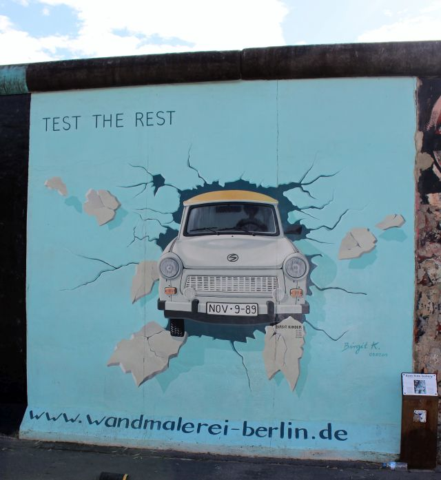 Ein Trabbi durchbricht in diesem Gemälde die Berliner Mauer.