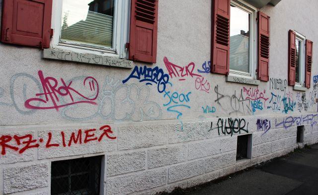 Helle Hausfassade mit Buchstaben und Wörtern in allerlei Farben.