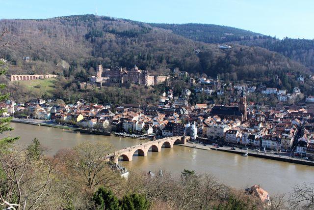 Im Blick die rötliche Schlossruine, die Alte Brücke über den Neckar, Kirchen und Häuser an engen Gassen.