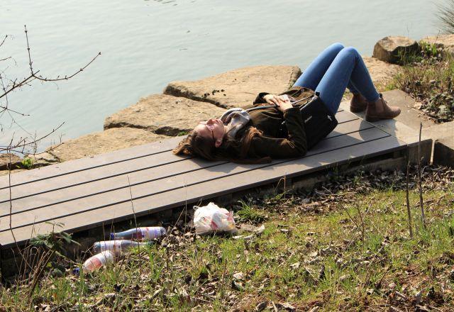Eine junge Frau mit blauer Jeans und brauner Jacke sonnt sich auf einer Holzbank. Dahinter liegen leere Flaschen und anderer Müll.