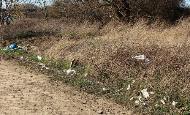 Müllteile verteilt an einem Böschungsrand, davor ein gepflasterter Platz.