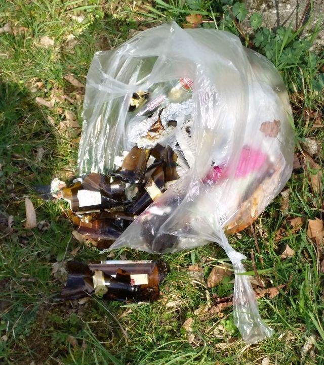 Aus einer weißen Plastiktüte quellen zerbrochene Flaschen und anderer Unrat.