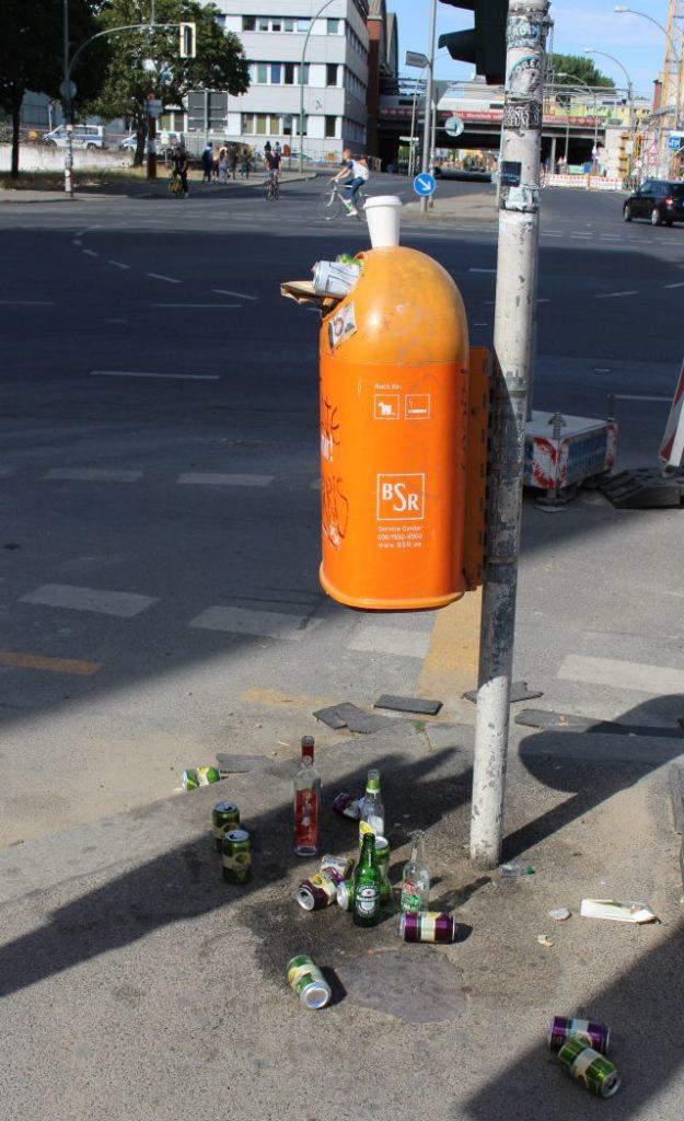 Ein voller orangefarbener Müllbehälter an einem Metallpfahl, darunter leere Flaschen.