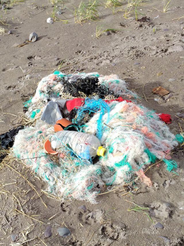 Ein Fischnetz hat sich am Strand abgelagert. Es besteht aus weißen engen Plastikmaschen.