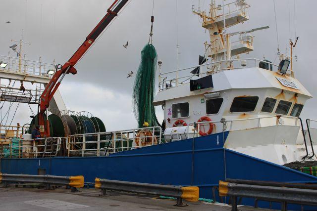 Fischtrawler. Es wird mit einem bordeigenen Kran ein Fangnetz hochgehoben.