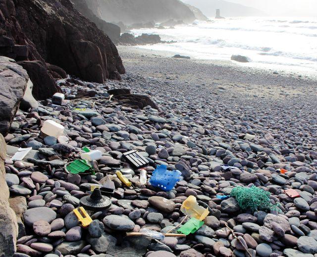 Große und kleine Plastikteile auf einem Steinstrand. Dahinter öffnet sich eine Bucht.