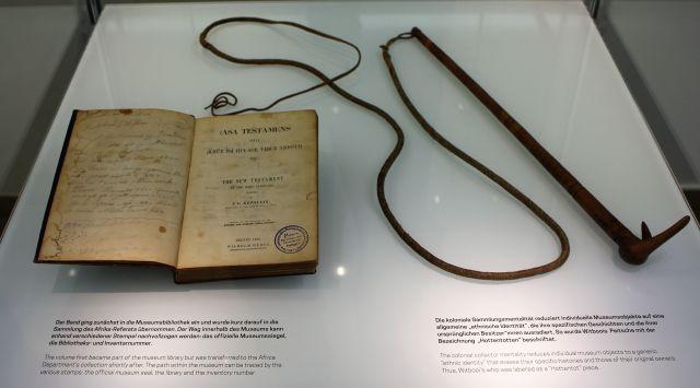 Eine aufgeschlagene Bibel mit einer daneben liegenden Peitsche.