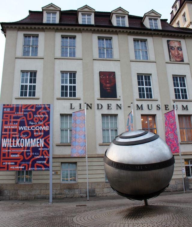 Das Linden-Museum un der Außenansicht. Der Schriftzug mit dem Namen auf einer hellen Fassade. Gauben am Dach. Davor eine stilisierte Weltkugel aus hellem Metall und ein Transparent mit dem Schriftug 'Willkommen' in vielen Sprachen.