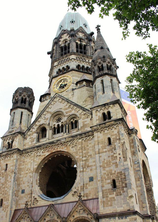 Die historischen Teile der Gedächntniskirche in Berlin. Am Turm eine goldene Uhr.