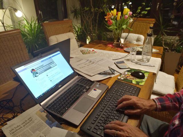 Laptop-Bildschirm mit Facebook und Händen an der Tastatur.