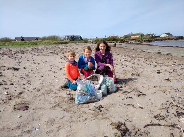 Drei Kinder mit dem aufgesammelten Strandgut.
